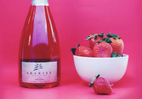 A red bottle of strawberry wine next to a bowl of strawberries