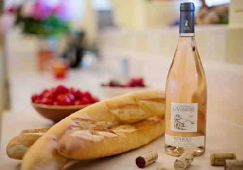 Transparent bottle of wine next to baguettes